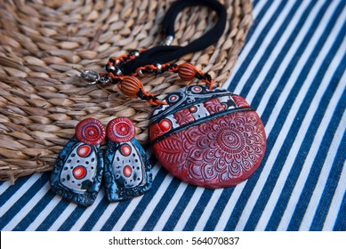Unique jewelry pendant and earrings of polymer clay. Fashion background. Handmade jewelery. Bohemian accessories.