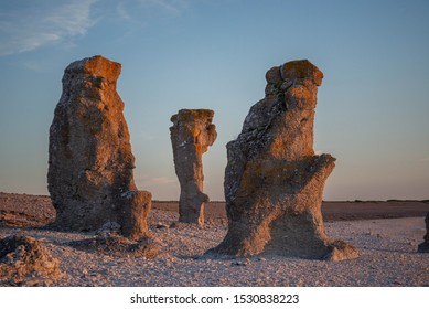 Unique limestone structures sitting on a stone beach in the setting sun casting by the ocean. Taken in Fårö, Gotland, Sweden.