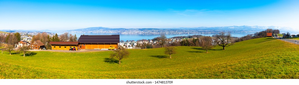 Unique panoramic skyline aerial view of Zurichsee, lake of Zurich with alps, blue sky background. Panorama view of Lake Zurich urban shoreline region, housing, green fields, Swiss Alps background.