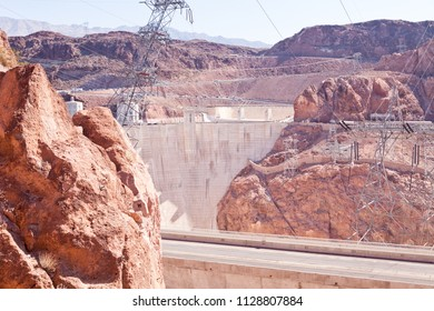 Unique perspective of the Hoover Dam with powerlines, towers and the road with cars in the background