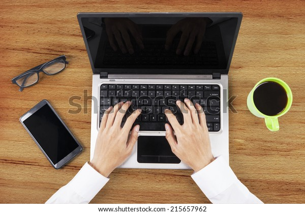Unique Perspectives of Hands working on table with laptop computer, smart phone, and a cup of coffee