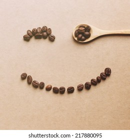 Unique perspectives of happy face shaped of coffee beans with wooden spoon, retro instagram filter effect