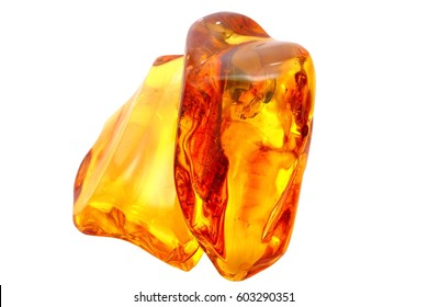 Unique pieces of transparent yellow amber on a white background. Two large reddish yellow polished amber. Macro photography of vintage pieces of amber