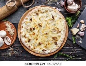 Unique pizza with cheese and walnuts. As package design element. Pizza on a black wooden background among spices