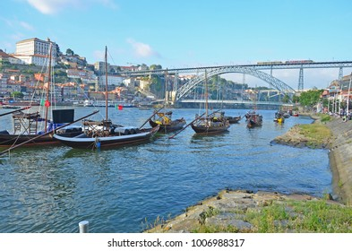 Unique Rabelo flat bottomed port boats on the River Douro at Porto, Portugal with the Dom Luis I bridge as a backdrop