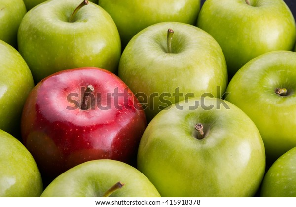 Unique. Red apple among group of green apples.
