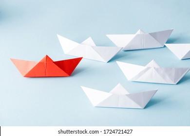 Unique red paper boat among white on blue background