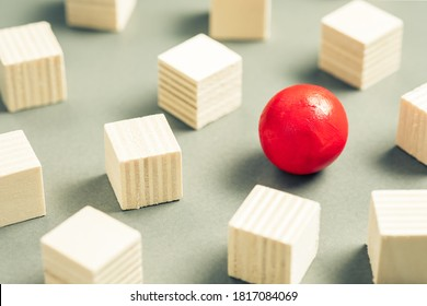 Unique red sphere in a group of sqaure cubes, small wooden objects for design and carpentry work, different and unique, positioning for advertising and business concept