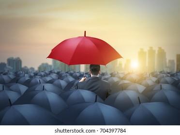 einzigartiger roter Regenschirm unter schwarzen Regenschirmen auf Stadthintergrund