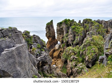 The unique ridged stone structures of New Zealand's Pancake Rocks are capped with greenery with pale blue ocean waters and washed out cloudy sky in the background.