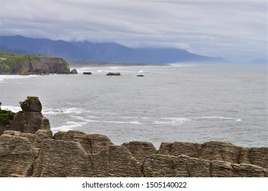The unique ridged stone structures of New Zealand's Pancake Rocks are in the foreground of murky grey ocean waters and distant blue mountains, capped with thick grey white clouds.