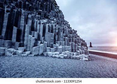 "A unique rock on the Atlantic Ocean. Basalt rocks ""Troll toes"". Location place Reynisfjara Beach, Iceland (Sudurland), Europe. Scenic image of popular european travel destination. Beauty of earth."