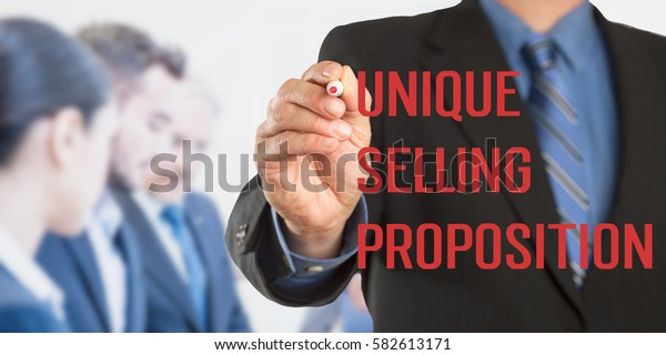 Unique Selling Proposition USP, Male hand in business wear holding a thick pen writing, with office team blurred in background, digital composing.