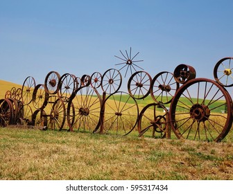Unique sight on the Palouse in eastern Washington of an old farm field  fence made of antique wagon & tractor wheels. This is on the Palouse Scenic Byway in Uniontown, WA on a warm, clear, summer day.