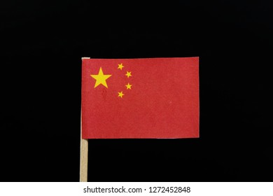 A unique and simply flag of China on toothpick on black background. A large golden star within an arc of four smaller golden stars, in the canton, on a field of red.