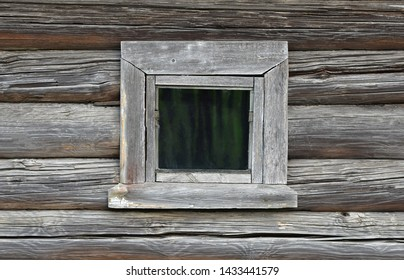 The unique texture of the old, rainy gray wall of the house, built of round logs with a small window