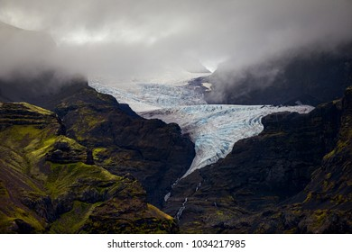 The unique twisting reach of Oraefajok Glacier in Iceland and it reaches down, out of the fog and into waterfalls.  Blue glacier ice is visible, as well as green moss covering rocks of the mountain