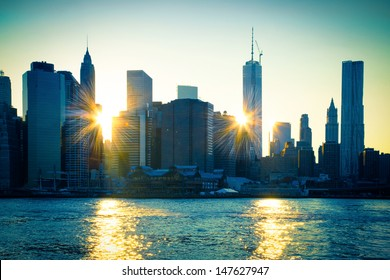 Unique view of East River and New York City  skyline with sun reflecting off buildings of lower Manhattan at sunset.