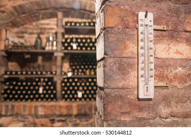 The unique vintage wine in the cellar. New bottles of wine in rows in wine cellar. Red and white wine stored in the brick cellar. thermometer on the wall of the cellar