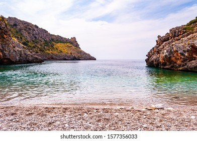 Unique white pebbles lying on amazing Cala Bianca beach surrounded by rocks and Tyrrhenian sea bay with crystal clear deep water full of underwater life. Cala Bianca beach in Campania region in Italy