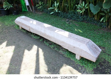 Unique wooden bench set on the green grass of the house backyard