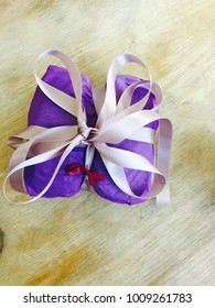 Unique wrapped gist with pink ribbon, red accent ribbon and purple paper