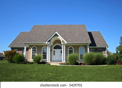 Uniquely designed suburban home with arches and porch.