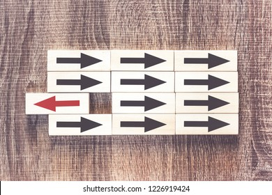 Uniqueness, difference, individuality and standing out from the crowd concept with red arrow pointing the opposite way from the black ones