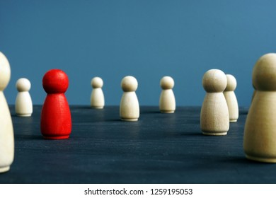Uniqueness, originality, difference and distinction. Wooden figures and red one.
