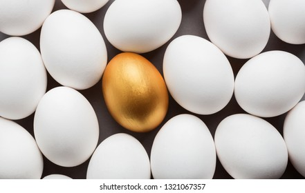 Uniqueness and success. One golden egg between group of white eggs, top view