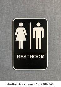 Unisex restroom sign, black and white gender neutral bathroom symbol on blue gray textured background