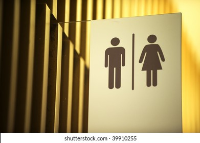 Unisex toilet sign against gold background