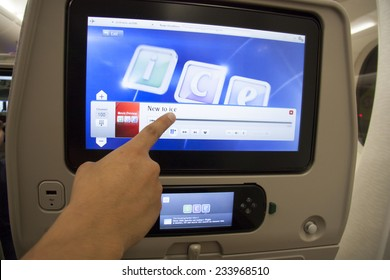 UNITED ARAB EMIRATES, EMIRATES AIRLINES FLIGHT, 27 JULY 2014 - Passenger pointing at the entertainment touch screen in a plane