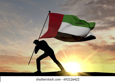 United Arab Emirates flag being pushed into the ground by a male silhouette. 3D Rendering