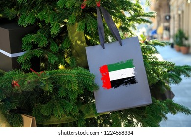 United Arab Emirates flag printed on a Christmas shopping bag. Close up of a gift bag as a decoration on a Xmas tree on a street. New Year or Christmas shopping, local market sale and deals concept.