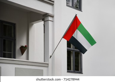 the United Arab Emirates flag. U.A.E. flag displaying on a pole in front of the house. National flag of UAE United Arab Emirates waving on a home hanging from a pole on a front door of a building.