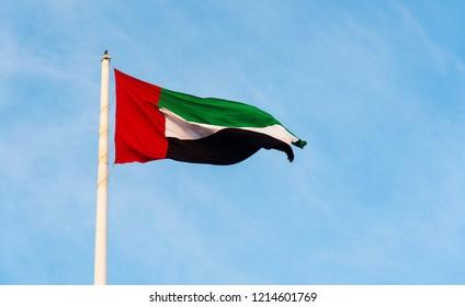 United Arab Emirates flag winding in the wind against blue sky