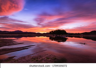 United Arab Emirates mountains view Wadi Al Qor Buraq Dam Sharjah and Ras Al khaimah at Sunrise time with water Reflection and red clouds