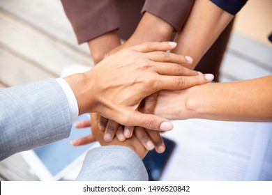 United diverse business team putting their hands together. Closeup of people stacking hands. Unity, teamwork or support concept