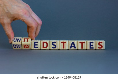 United or divided states of Amerika. Male hand flips wooden cubes and changes the inscription 'United States' to 'Divided States'. Beautiful grey background, copy space.