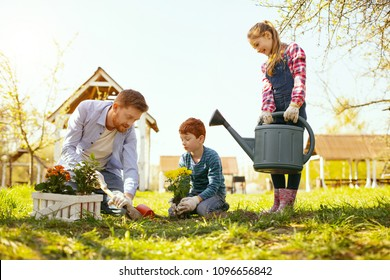 United family. Cheerful nice girl holding a watering can while helping her family
