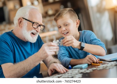 United family. Positive happy cheerful grandfather and grandson holding puzzle pieces and putting them together while having fun