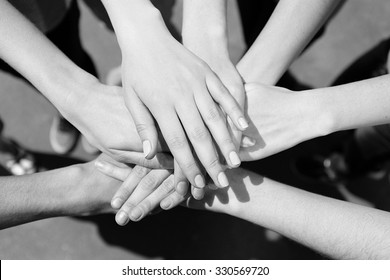 United hands outdoors.  Black and white retro stylization