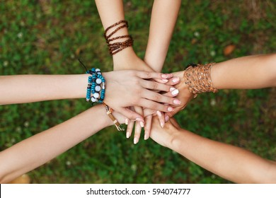 United hands of young females, top view. Stylish girlfriends in boho hippie bracelets at green grass background. Togetherness and support, youth fashion and active lesiure. Women friendship
