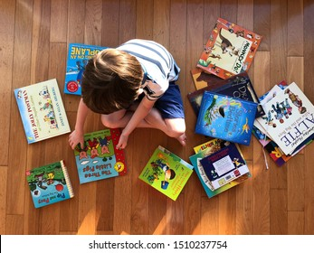 United Kingdom 9 September 2019: little boy sitting on the floor surrounded by picture books and stories