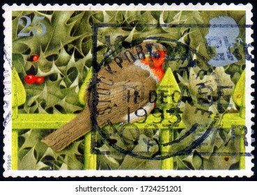 UNITED KINGDOM - CIRCA 1995: stamp printed by UK shows animal European Robin (Erithacus rubecula) on Railings and Holly, circa 1995