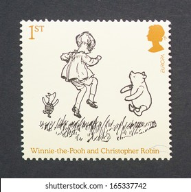 UNITED KINGDOM - CIRCA 2010: a postage stamp printed in United Kingdom showing an image of cartoon characters teddy bear Winnie-the- Pooh, the boy Christopher Robin and the pig Piglet, circa 2010.