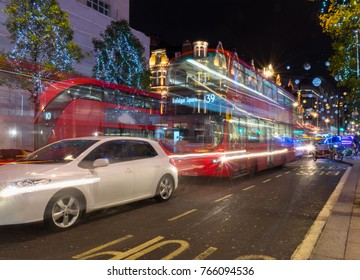 United Kingdom at night with moving bus and cars leaving light traces. Christmas mood. Christmas lights decoration at Oxford street.