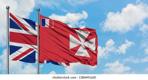 United Kingdom and Wallis And Futuna flag waving in the wind against white cloudy blue sky together. Diplomacy concept, international relations.
