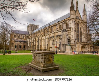 UNITED KINGDOM, WINCHESTER - APRIL 4, 2015: Winchester Cathedral with dramatic clouds and tomb in the foreground